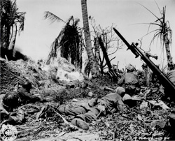 """Men of the 7th Division using flame throwers to smoke out Japs from a block house on Kwajalein Island, while others wait with rifles ready in case Japs come out."" Cordray, February 4, 1944. NARA photo."